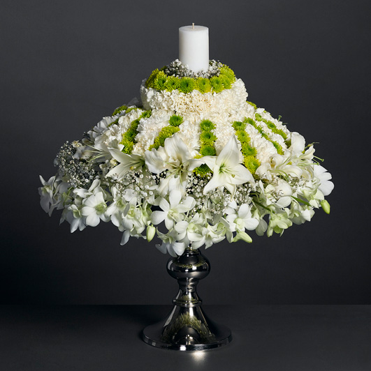 White masterpiece of orchids and lilies, topped with a scented candle.