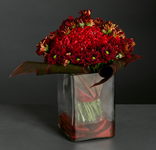 Scarlet carnations and crimson chrysanthemums in a glass cube